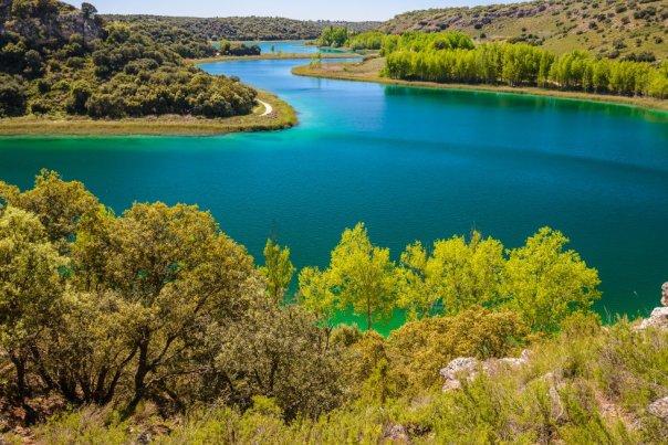 Dividido entre las provincias manchegas de Albacete y Ciudad Real (Castilla-La Mancha), en mitad de Campo de Montiel, y más popular que algunos parques nacionales, el parque natural de las Lagunas de Ruidera ocupa 4.000 hectáreas. Entre la más alta, La Blanca, y la última, La Cenagosa, existe un desnivel de 120 metros que el agua va salvando mediante una sucesión de cascadas, saltos de agua y torrentes, a lo largo de 25 kilómetros. Son, con alguna excepción, lagunas pequeñas, que incluso pueden llegar a secarse durante el verano. En su cota más alta, Cabeza de San Pedro, se encuentran las ruinas del castillo de Rochafrida y la cueva de Montesinos. Abajo espejea el pantano de Peñarroya, al pie del castillo homónimo. En la imagen, la laguna Conceja, en la que está prohibida la navegación. Más información: turismocastillalamancha.es
