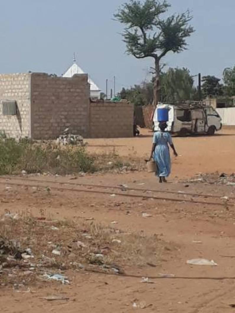 Mulher caminha com balde d'água na cabeça em Dahra, Senegal.