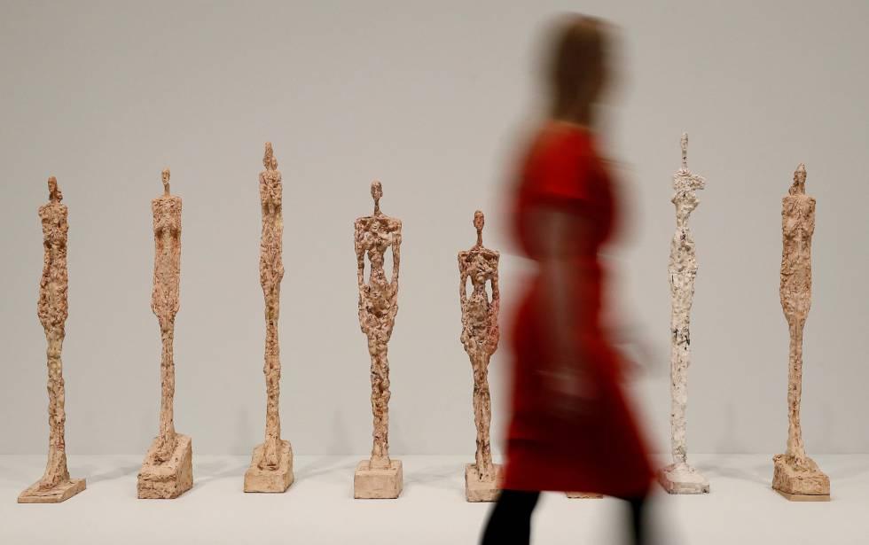Una visitante pasea ante la serie de esculturas 'Mujer de Venecia', de Alberto Giacometti, en la Tate Modern de Londres.