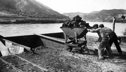 Unos trabajadores cargan un barco de carbón en el río Ebro en los alrededores de Mequinenza a principios del siglo XX.