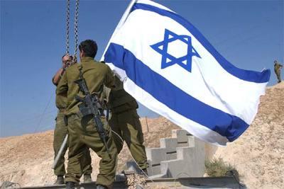 Tres soldados retiran una bandera israelí ayer en una de las entradas de la ciudad de Jericó.