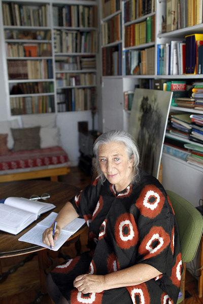 La poeta Clara Janés, sentada a la mesa heredada de su padre en la que traduce. A su espalda, una fotografía tomada por su hija.