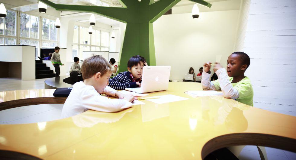 Un grupo de niños en una de las mesas orgánicas diseñadas por Rosan Bosch Studio, en la que los alumnos deciden a qué distancia quieren trabajar.