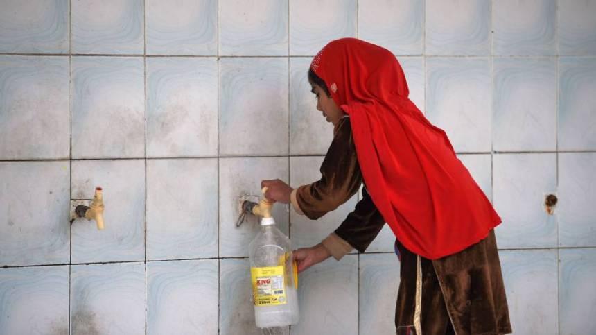 Una niña recoge agua en una planta de purificación en Islamabad