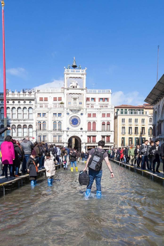 Turistas na praça de São Marcos, em Veneza, durante as inundações causadas pela 'acqua alta'.