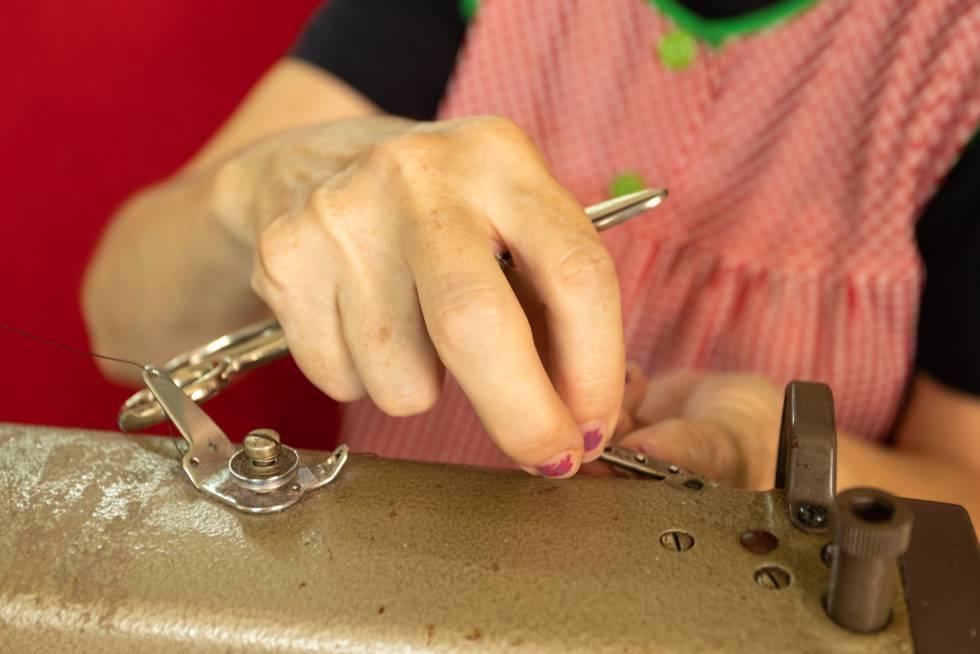 Antonia Rico coloca un hilo en la máquina de coser.