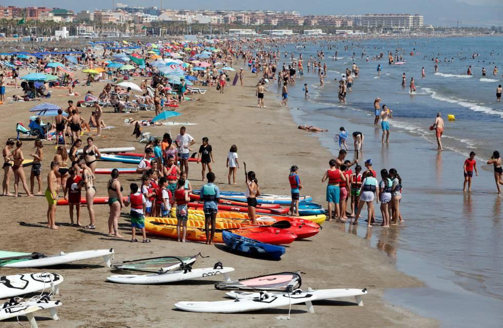 Miles de turistas en la playa de la Malvarrosa de València .