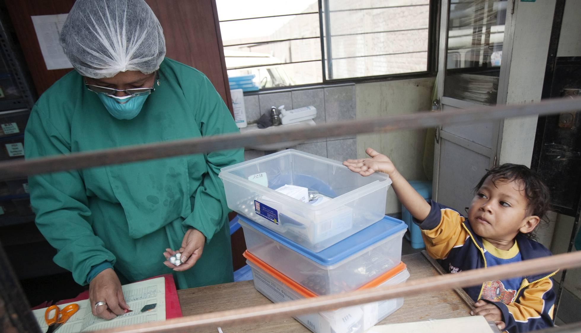n niño con tuberculosis tiende la mano para coger las píldoras de pie junto a una enfermera en un puesto de salud en las afueras de Lima (Perú) REUTERS