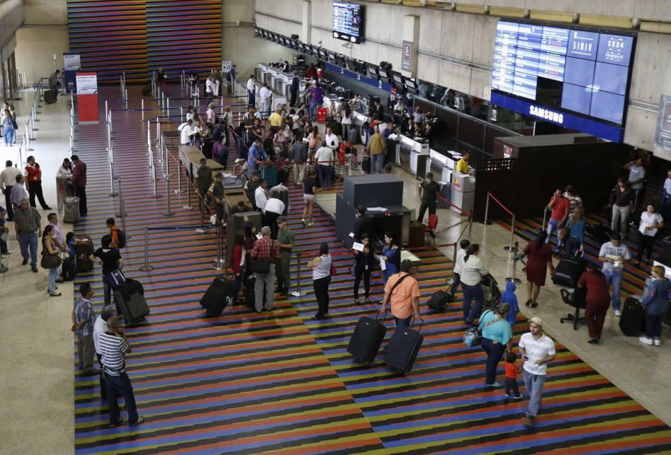 Passageiros na área de despacho de bagagens do aeroporto Simón Bolívar.