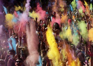 Un grupo de personas se cubren con polvos de colores en una fiesta de origen indio que celebra la primavera.