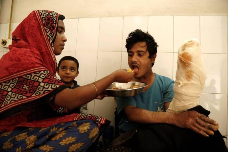 Abul Bajandar recibe comida de manos de su esposa, Halima Akter.