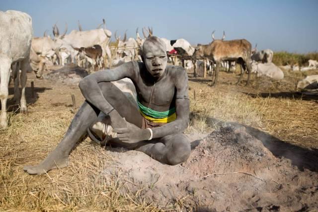 Un joven mundari con corsé de cuentas tradicional se aplica ceniza en el cuerpo, Sudán del Sur.