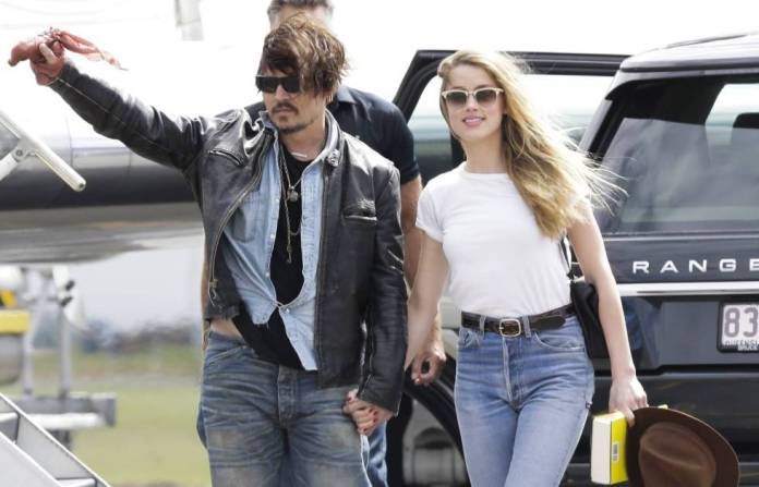 Johnny Depp, with his hand bandaged, and Amber Heard, on his arrival in Australia in April 215.
