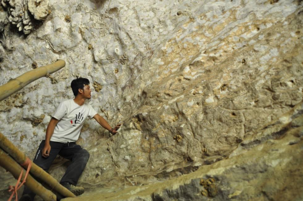 Uno de los miembros del equipo observa el mural hallado en la isla de Célebes (Indonesia).