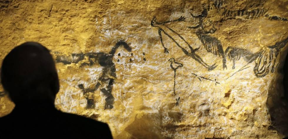 Una persona observa la pintura rupestre conocida como el hombre pájaro en la cueva de Lascaux (Francia).