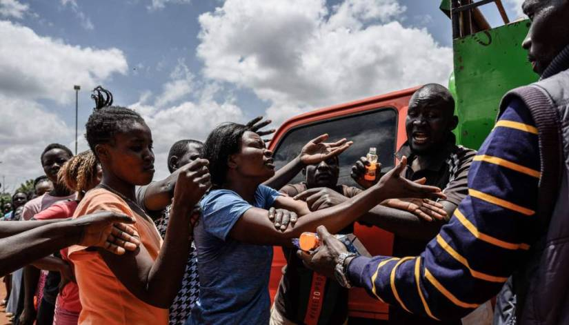 A woman receives food on April 2, 2020, during a distribution by a group of Kenyan volunteers called Team Pangaj. They deliver flour, beans, milk and juice to some 900 people in Kibera, one of the poorest suburbs in Nairobi, the capital of Kenya.