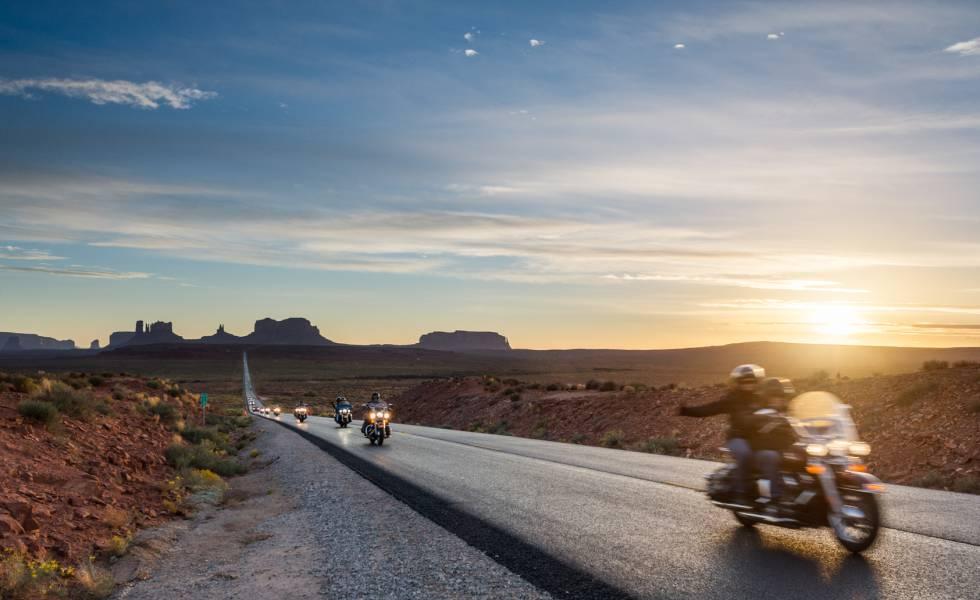 Motoristas curzando por carretera el parque tribal de los indios Navajo, con Monument Valley (Utah) al fondo.