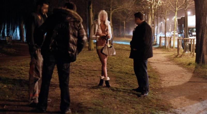 Dos agentes interrogan a una prostituta y a un cliente durante una operación policial en París en marzo de 2012.