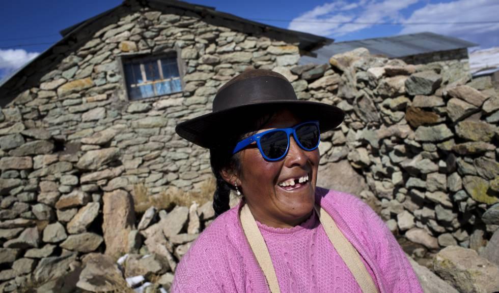 Una mujer peruana sonríe ante las bromas que le juegan sus vecinos por sus lentes de sol.