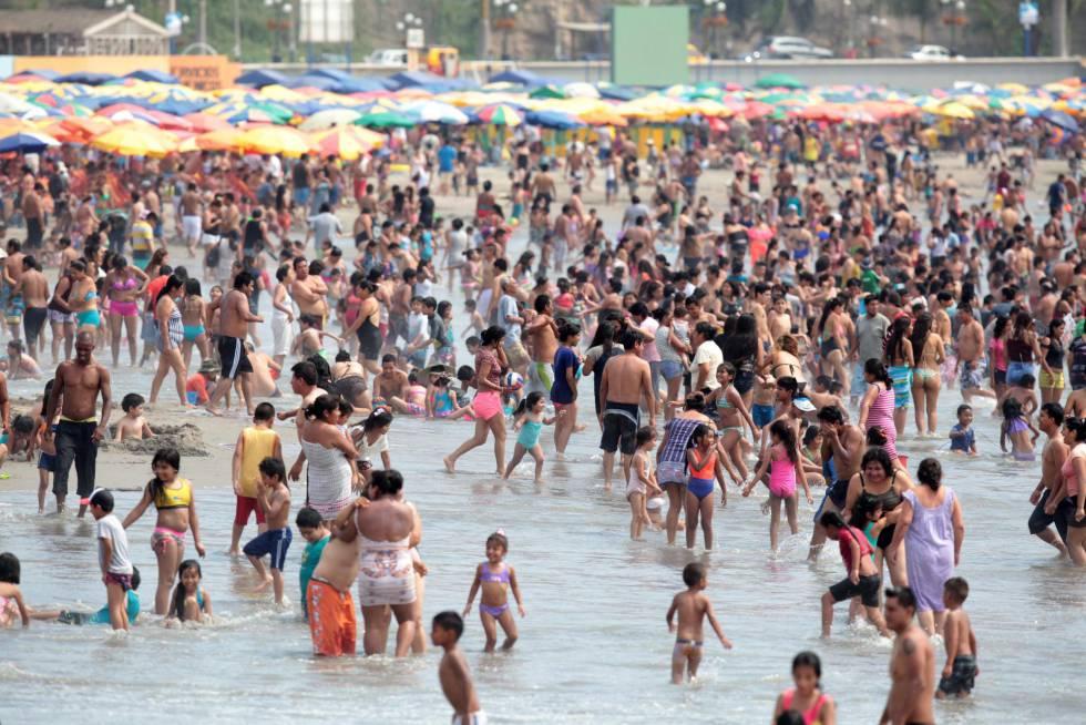 Un grupo de veraneantes toma sol en una playa de Lima.