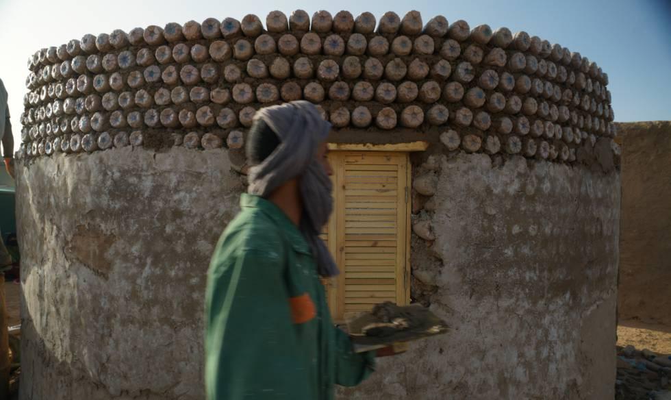 Un hombre saharaui trabaja para terminar una vivienda de botellas en el campamento de Tinduf.