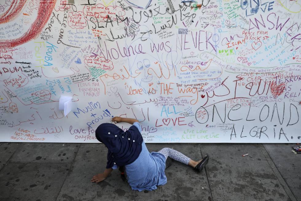 Una niña escribe una dedicatoria en el muro junto a la mezquita.