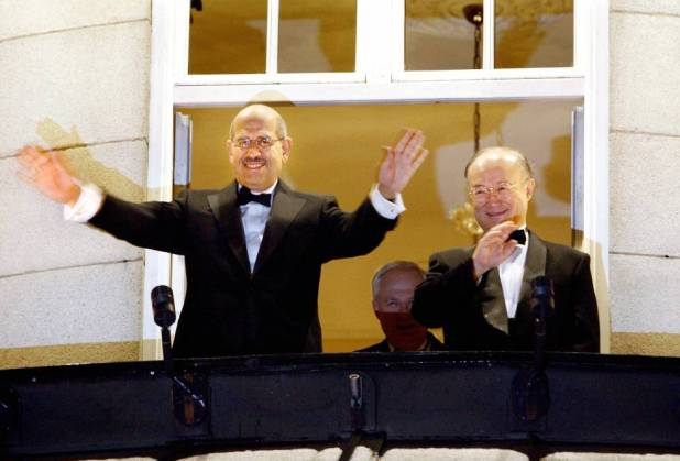 El director de la Agencia Internaional de la Energía Atómica, Mohamed El Baradei (izquierda) saluda desde su hotel tras conocer la concesión del Nobel, en 2005.