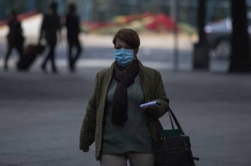Una mujer con cubrebocas por la contaminación.