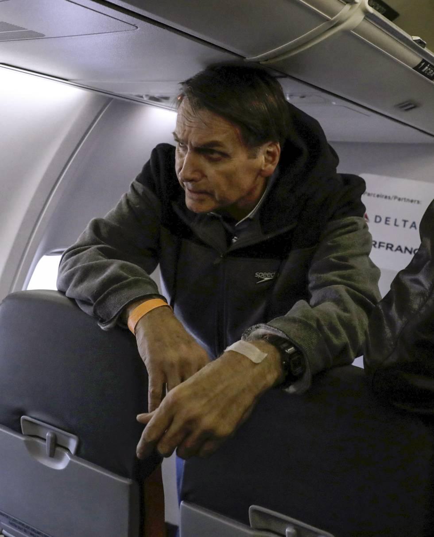 Bolsonaro, a bordo de un avión en septiembre. Abajo, el día que recibió una puñalada.