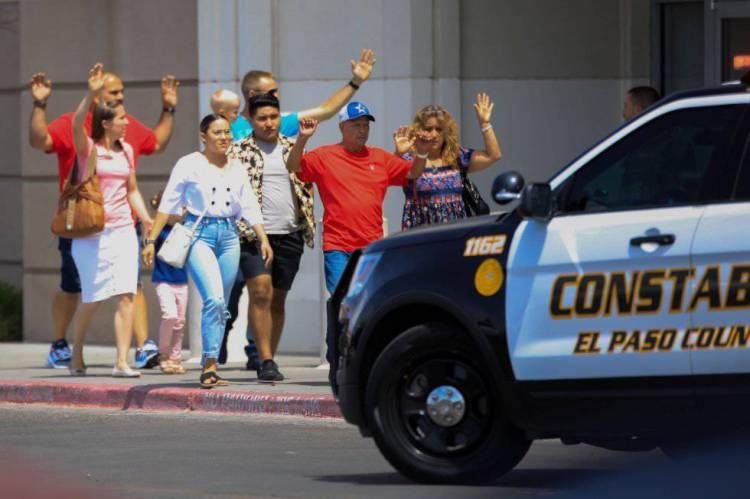 Un grupo de personas sale con las manos en alto del Walmart de El Paso (Texas, EE UU) donde se ha producido el tiroteo.