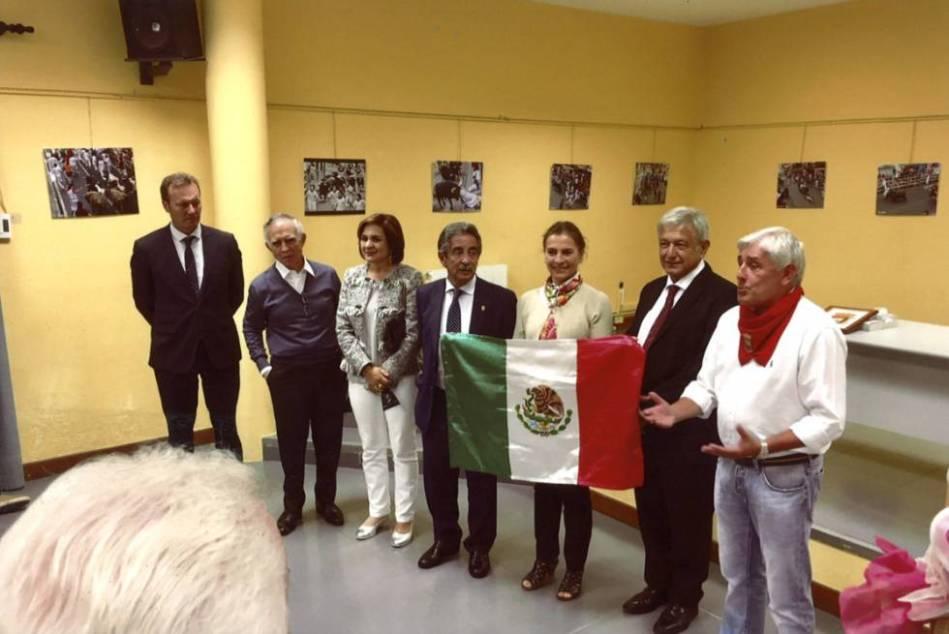 López Obrador sujeta la bandera de México durante su visita a Ampuero del año pasado. A la derecha, un pariente de Cantabria.