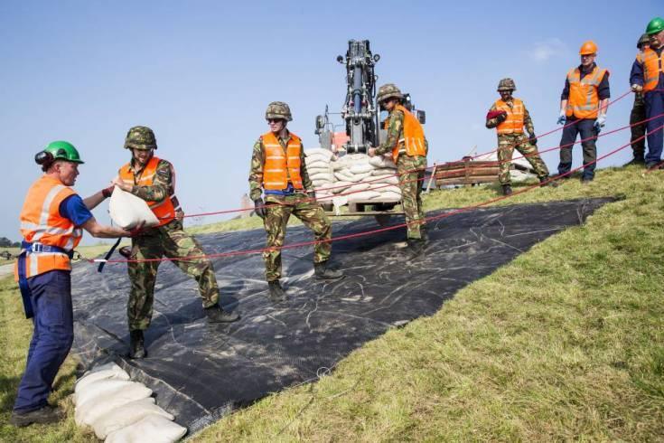 Varios soldados colaboran para reforzar un dique en Holanda.rn
