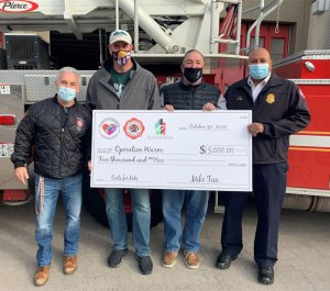Operation Warm accepting donation check from Mice Tice Foundation, Twin Cities Firefighters, and Epic Property Services.