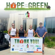 Four people at Spare Key's Hope on the Green event holding a Thank You sign listing the sponsors.