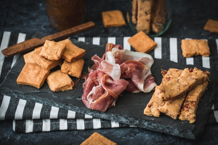 A slate tray of two types of manchego cheese crackers and proscuitto ham