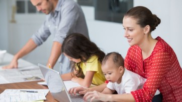 Smiling mother working on laptop with baby