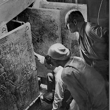 "Howard Carter (kneeling), an Egyptian workman, and Arthur Callender at doors of burial shrines in Pharao Tutankhamen's tomb. Description and date rely on the Griffith Institute, Oxford (1924-01-04) as well as on Howard Carter's diary. According to the latter, the shrines were opened 1924-01-03, Burton present, while the diary notes ""records"" by Burton for 1924-01-04 only, so perhaps we see a kind of reenactment. Actually some work was needed for opening the third and the fourth door, unlikely with left-hand wings almost closed as on the present photograph. Griffith Institute, Oxford Burton Photo No. P0643"