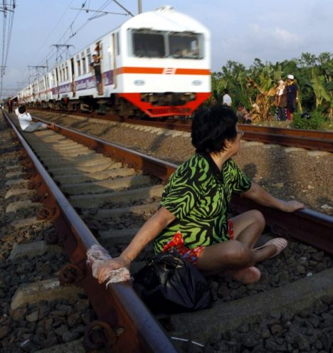 143751-a-woman-sits-on-railway-tracks-in-rawa-buaya-in-indonesias-west-java-p
