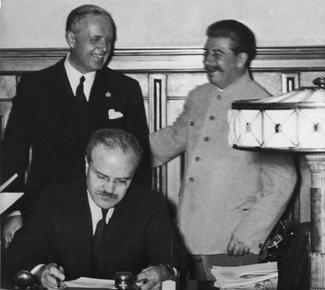 23rd August 1939: Joachim von Ribbentrop (1893-1946), German foreign minister, Soviet premier Joseph Stalin, and Viachislav Mikhailovich Molotov (1890-1986) (seated), Soviet foreign minister, sharing a joke at the signing of the Molotov/Ribbentrop Pact, a.k.a. the Soviet-German Non-Aggression Treaty. The treaty divided the Republic of Poland between Germany and Russia. (Photo by Hulton Archive/Getty Images) Hulton Archive/Toronto Star