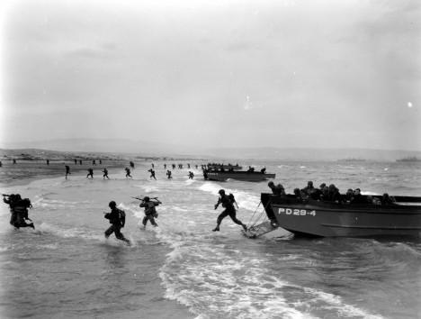 Des unités US se ruent depuis leur LCVP sur la plage. LCVP immatriculés PD29-4, PD29-3 et PD29-2. Le APD-29 est l' USS Barry (Ex-DD-248), ce n'est qu'en janvier 1944 qu'il devient le transport de troupes rapide APD-29, conversion à Charleston Navy Yard, du 31 Déc. 1943 au 17 Févr. 1944. Puis part pour Mers-el-Kébir, Algérie, où il y arrive le 30 avril. Il mène des entrainements amphibies (photo), en vue du débarquement de Provence, où il y participe. Puis le Pacifique. pour aller plus loin : http://www.destroyerhistory.org/flushdeck/ussbarry.html