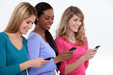 Three female students texting.