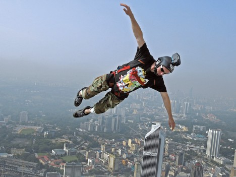 epa01907372 A base jumper leaps from the 380 metres high Kuala Lumpur Tower in Kuala Lumpur, Malaysia, 23 October 2009. Some 98 base jumpers from 18 countries took part in the annual KL Tower International Jump. BASE (Building, Antenna, Span and Earth)-jumping is an extreme sport where parachutists jump off tall buildings and structures instead of aircraft.  EPA/SHAMSHAHRIN SHAMSUDIN