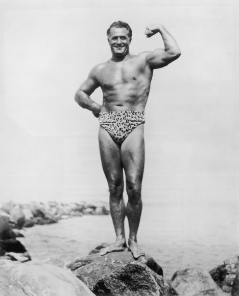 circa 1945: Full-length portrait of Italian-born bodybuilder Charles Atlas (born Angelo Siciliano) (1893 - 1972) flexing his bicep while posing in a leopard print swimsuit on a rock by the water's edge. (Photo by Hulton Archive/Getty Images)