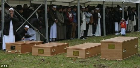 Dr. Al Sattar (vlevo) se modlí nad rakvemi sve rodiny