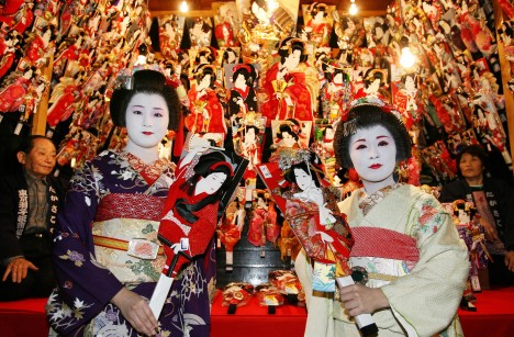 Tokyo, JAPAN: Japanese geisha girls clad in kimonos admire wooden battledores called 'hagoita' at Sensoji temple in Tokyo, during a preview of the three-day annual 'hagoita' fair 16 December 2006. The hagoita is used for a traditional girls game played during the New Year's celebrations. AFP PHOTO/Toru YAMANAKA (Photo credit should read TORU YAMANAKA/AFP/Getty Images)