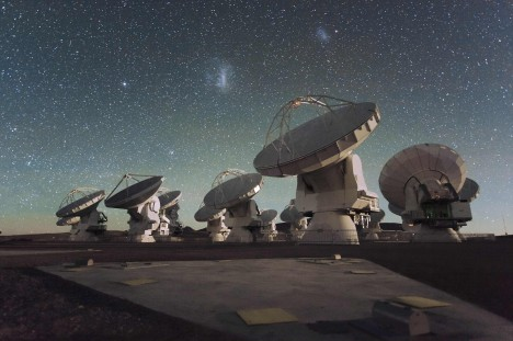 Antennas of the Atacama Large Millimeter/submillimeter Array (ALMA), on the Chajnantor Plateau in the Chilean Andes. The Large and Small Magellanic Clouds, two companion galaxies to our own Milky Way galaxy, can be seen as bright smudges in the night sky, in the centre of the photograph.