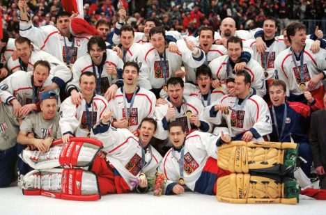 Czech Republic goalkeepers Dominik Hasek (L front) and Roman Cechmanek (R front) lay in front of the rest of the team as they pose with their medals after winning the final of the Olympic ice hockey tournament at the Big Hat Stadium in Nagano February 22. [The Czech Republic beat Russia 1-0 to claim the gold medal.] - RTXIIXA