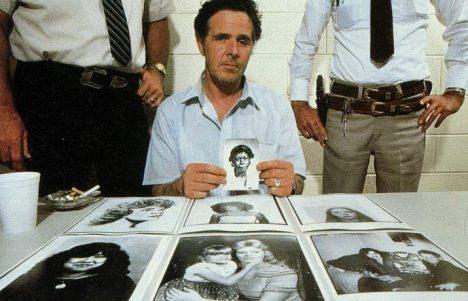 Henry Lee Lucas pozuje s fotkami svých oběti.