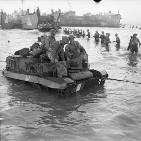 A Universal carrier is towed ashore, as troops unload ammunition from a landing craft in the background, 10 July 1943.
