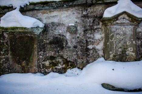 Zvláštní kamenná lebka na hřbitovní zdi.